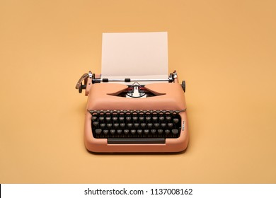 Chic retro typewriter with a paper sheet on the yellow background in the studio. Horizontal.