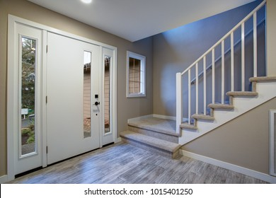 Chic traditional entryway, beige staircase with white wooden spindles and front door framed by sidelights.