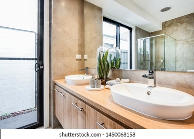 A chic washroom style with two sink and faucets and a planter in the center to add some color and style.