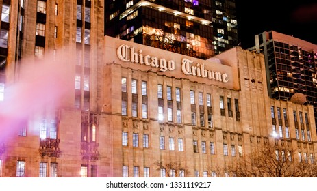 Chicago, IL—Mar 4, 2019; steam rises from the street in front of old granite building in downtown with the Chicago Tribune logo on its side and other buildings in the background