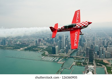 CHICAGO - AUGUST 16: Sean Tucker of Team Oracle flies in front of the Chicago skyline during the Chicago Air and Water Show Media Day on August 16, 2012 in Chicago.