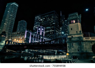 Chicago city riverwalk promenade at night with vintage drawbridge and illuminated urban downtown buildings.