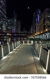 Chicago city riverwalk promenade at night with vintage drawbridge, illuminated urban downtown buildings and the moon.