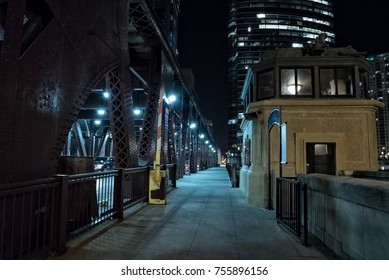 Chicago city vintage river drawbridge with tender house and urban downtown buildings at night.