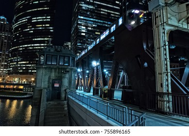Chicago city vintage river drawbridge with elevated CTA subway train and urban downtown buildings at night.
