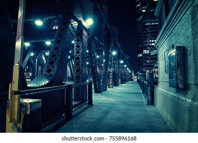 Chicago city vintage river drawbridge with urban downtown buildings at night.