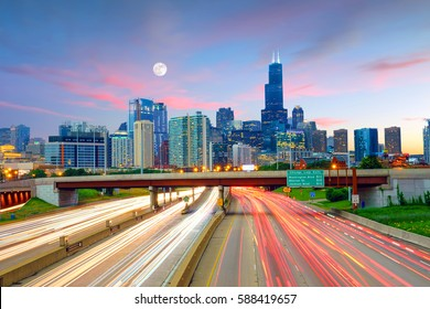 Chicago downtown skyline at twilight with highway and traffic.