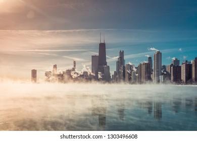 Chicago Downtown with winter fog on Lake Michigan. Arctic polar vortex. Sunbeam