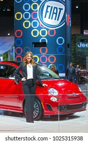 CHICAGO - February 9: A model poses with a red Fiat at the Chicago Auto Show media preview February 9, 2018 in Chicago, Illinois.