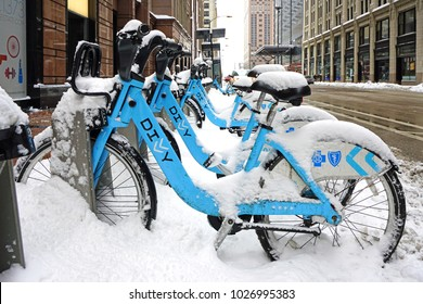 CHICAGO, IL -12 FEB 2018- Winter in Chicago. Snow covers Divvy bike shares blue Bixi bicycles parked on the street in downtown Chicago.