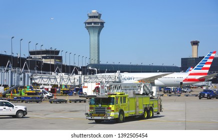 CHICAGO, IL -21 APR 2019- View of a yellow firetruck near an American Airlines (AA) airplane at Chicago O'Hare International Airport (ORD).