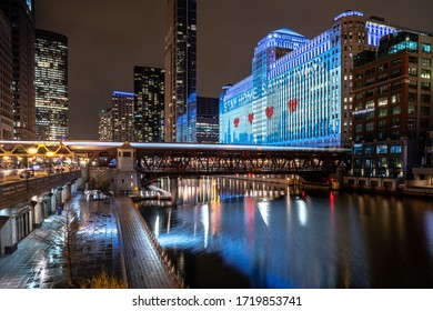 """Chicago, IL - April 22nd, 2020: A CTA train passes over the Wells Street bridge in front of Merchandise Mart's, """"Stay Home Save Lives"""" display during the COVID-19 pandemic and stay at home orders."""