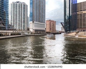 Chicago, IL - April 9th, 2017: A white Chicago tour boat full of tourists makes the curve in the river heading north along Wolf Point passing by the raised Chicago and Northwestern Railway Bridge.