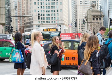 Chicago, IL, August 17, 2017: Young woman waits to cross the street downtown Chicago, during the rush hour commute. More than half a million people work downtown Chicago.