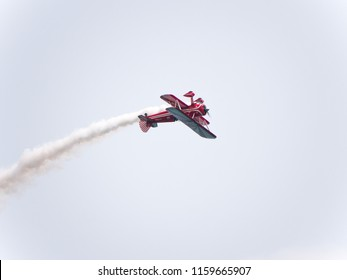 Chicago, IL - August 18th, 2018: Female aerobatic Susan Dacy performs stunts in 'Big Red' leaving trails of smoke and entertaining spectators watching from below at the annual Air and Water show.