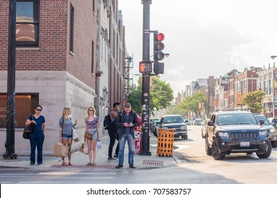 Chicago, IL, August 30, 2017: People with shopping bags waiting to cross the street in the River West neighborhood, an area popular for its close proximity to downtown Chicago.