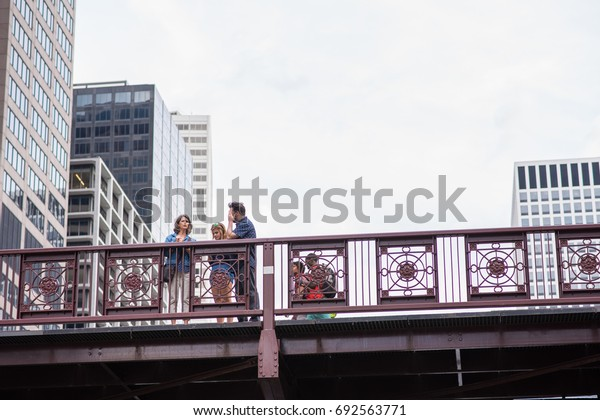 Chicago, IL, August 5, 2017: View from below of a family enjoying the scenery downtown Chicago. Millions of people visit Chicago each year, and the downtown area is very scenic.