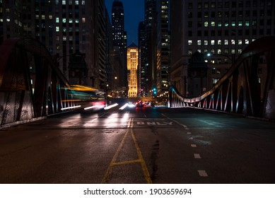 Chicago, IL December 16, 2020, car light trails at night, looking over the LaSalle Street Bridge towards the CTA Chicago Transit Authority elevated train tracks up above LaSalle Street with the Chicago