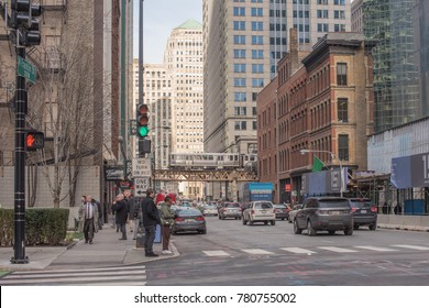 Chicago, IL, December 19, 2017: Typical street scene downtown Chicago. People wait at the crosswalk while the L train (elevated train) passes in the distance.