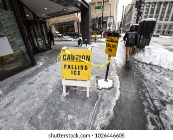 Chicago, IL - February 12th, 2018: Falling ice warning signs litter the sidewalks in downtown Chicago as the warming weather loosens ice and snow from the roofs and facades of high rise buildings.