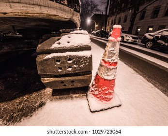 Chicago, IL - February 17th 2018: Road construction and excavation equipment sits on a quiet winter night after a light snow earlier in the evening on a residential street in Edgewater neighborhood.