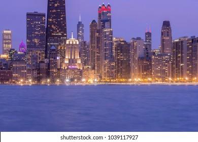 CHICAGO, IL - FEBRUARY 2018 - A Close Up Long Exposure Twilight Shot of the Chicago Icon, the Drake Hotel Nestled Among the Illuminated Skyline over Lake Michigan
