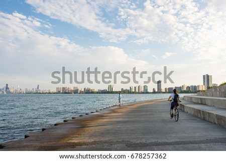 CHICAGO, IL, July 15, 2017: A cyclist rides along the park area at Montrose Beach, a popular area in Chicago during summer that overlooks the skyline.