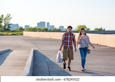CHICAGO, IL, July 16, 2017: Young couple walks home after errands, through the popular park at Montrose Beach. Chicago offers miles of lakeside walking paths and is a very walkable city.