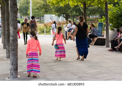 CHICAGO, IL, July 19, 2017: Two sisters dressed to match in bright clothing walk with their mother at Navy Pier for a family outing. Navy Pier attracts millions of visitors each year.