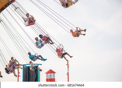 CHICAGO, IL, July 19, 2017: People smiling and waving during their ride on the famous Pepsi Wave Swinger, a popular ride at Navy Pier, which attracts millions of visitors each year.