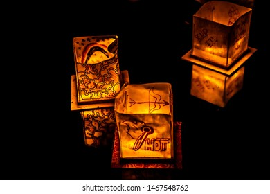 Chicago, IL - July 20th, 2019:  Glowing orange lanterns float across the South Lagoon at the Water Lantern Festival in Lincoln Park Saturday evening with music, food and family friendly activities.