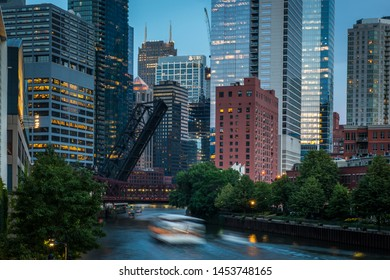 Chicago, IL - July 9, 2019: A tour boat glides along the Chicago River on a summer's evening near the Kinzie Street Bridge in Chicago, Illinois. (1069)