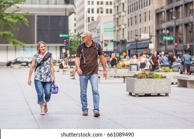 CHICAGO, IL, June 15, 2017: Middle aged couple crosses the plaza at Jackson street, downtown, after work. Over half a million people work downtown Chicago, and rush hour is always busy and exciting.