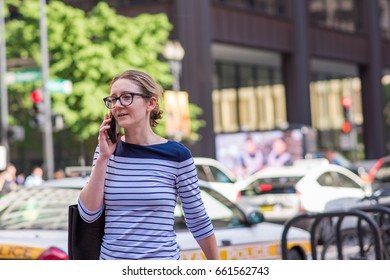 CHICAGO, IL, June 15, 2017: Young woman smiles and talks on her phone while walking home from work, downtown. Cell phones are ubiquitous in the city, and many people text and talk while walking.