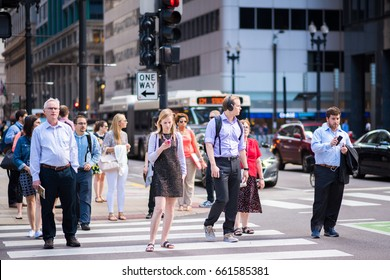 CHICAGO, IL, June 15, 2017: Stylish young woman checks her phone while waiting to cross the street, downtown. Cell phones are ubiquitous in the city, and people sometimes text while they walk.