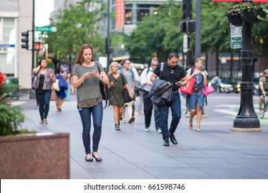 CHICAGO, IL, June 15, 2017: Young woman checks her phone while walking, downtown Chicago. Cell phones are ubiquitous in the city, and many people text and check social media while walking or commuting