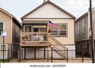"CHICAGO, IL, June 21, 2017: ""All American"" home in the West Town neighborhood. A flag waves overhead as an older woman sits on her porch on a summer day. Wood siding and traditional architecture."