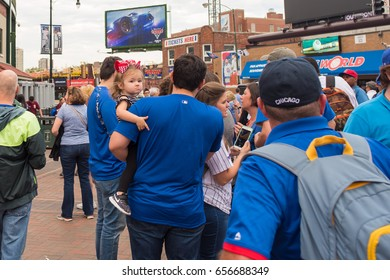 CHICAGO, IL, June 8, 2017: A little girl stays safe in her father's arms, amidst the huge crowd at Wrigley Field on game day. The Chicago Cubs are the reigning World Champions.