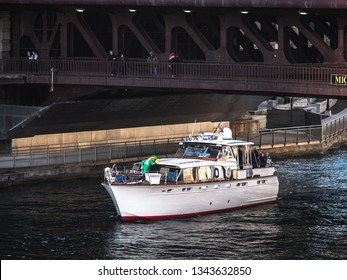 Chicago, IL - March 16th, 2019:  A boat tricked out with a blow up leprechaun and decorations cruises down the Chicago River prior to the kickoff of the annual St. Patrick's Day river dyeing event.