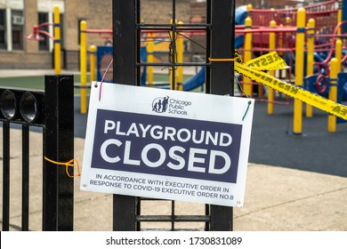 Chicago, IL - May 3rd, 2020: Yellow restricted area caution tape and posted sign blocks off a playground at Swift School part of Chicago Public Schools in response to executive order number 8.
