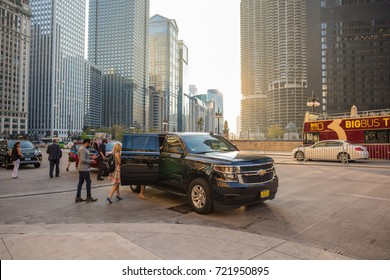 Chicago, IL, Sept. 23, 2017: A young couple gets into a cab after exiting their hotel, downtown Chicago, in the Loop. Cabs are ubiquitous in Chicago, where millions of people visit each year.