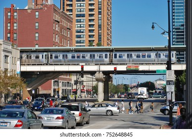 """CHICAGO, IL - SEPTEMBER 15, 2012: Elevated """"L"""" Train stops at a raised station at State Street and Roosevelt Street as commuters and pedestrians move below"""