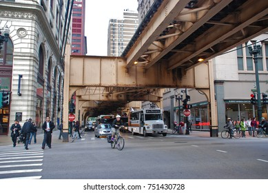 """CHICAGO, IL - SEPTEMBER 23, 2011: Buses, bikes, cars, and pedestrians move through the intersection of State St. and Van Buren St. as the famous Downtown Chicago """"L"""" elevated train tracks hover above."""