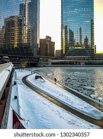 Chicago, IL / USA - 2/1/19: Commuters walk on Wacker Drive and the riverwalk alongside a frozen Chicago River on a frigid evening in January