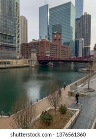Chicago, IL / USA - 3/7/19: Commuters walk along a frozen Chicago River on winter morning