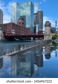 Chicago, IL / USA - 6/26/19: Cityscape is reflected into splash pad puddle water on the riverwalk as pedestrians walk alongside the Chicago River during summer