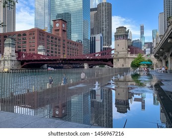 Chicago, IL / USA - 6/26/19: Reflection of Chicago cityscape in splash pad puddle while tourists and commuters utilize the riverwalk during summer