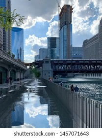 Chicago, IL / USA - 6/26/19: Stormy sky reflected in the splash pad puddle of the Chicago River riverwalk as pedestrians walk by and el train crosses water.