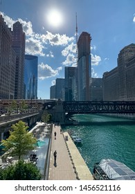 Chicago, IL / USA - 7/10/19: Summer in Chicago riverside, where pedestrians & tourists enjoy the riverwalk, boats docked, & splash pad fountain provides water while el train crosses water and Wacker