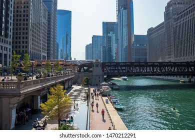 Chicago, IL / USA - 7/23/19: Busy Chicago scene at Chicago River with el train crossing water, children playing at splash pad, Wacker Dr. commuters, recreational boats on water.